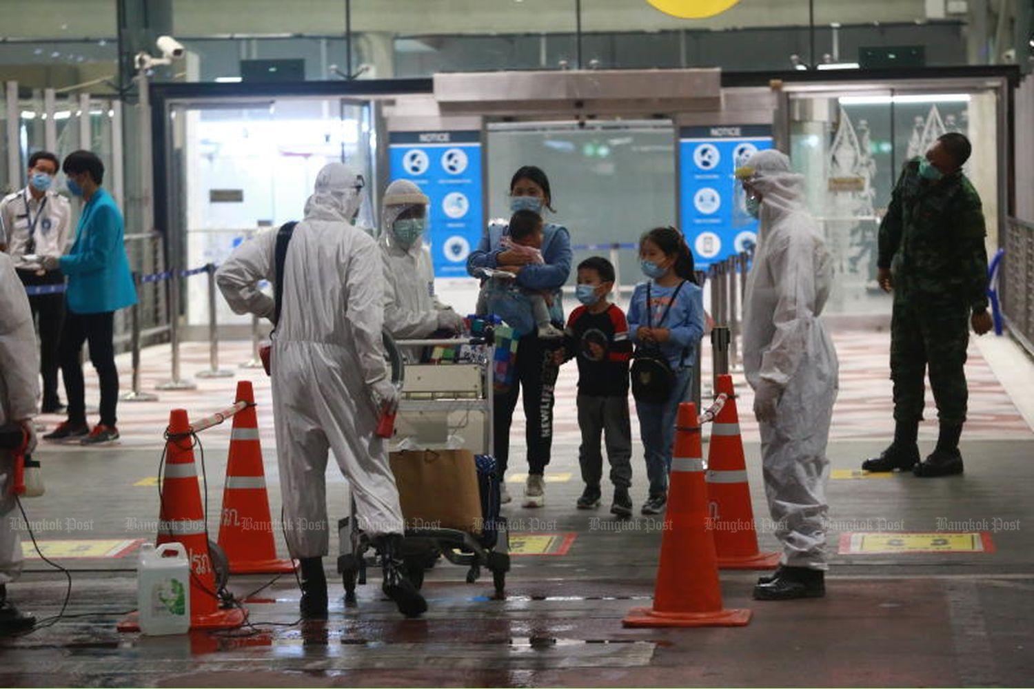 Health officials check the body temperature of visitors from China arriving at Suvarnabhumi airport from Shanghai on Oct 21, 2020. (Photo by Somchai Poomlard)