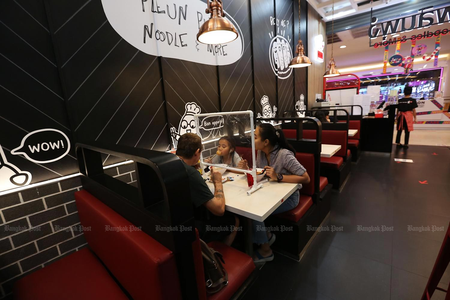 A family dines at a restaurant at The Mall Bang Kapi department store with a shield in place to prevent the spread of Covid-19.(Photo by Varuth Hirunyatheb)