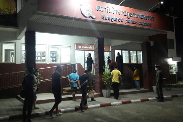 Arrested gamblers arrive at a police station in Nakhon Sawan on Monday night after police raided a house in Banphot Phisai district. They had all come from neighbouring Pichit to try their luck. (Photo: Chalit Poomruang)