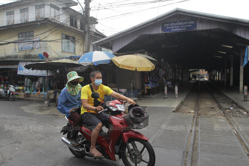 A motorcyclist and pillion rider pass Mahachai railway station in Muang district of Samut Sakhon, the initial hotspot of the Covid-19 second wave. (Photo: Arnun Chonmahatrakool)