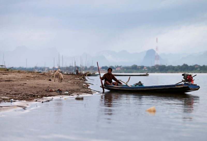 FILE PHOTO: A dog walks towards a fisherman sitting in a boat on the Mekong River in Nakhon Phanom July 24, 2019. (Reuters)