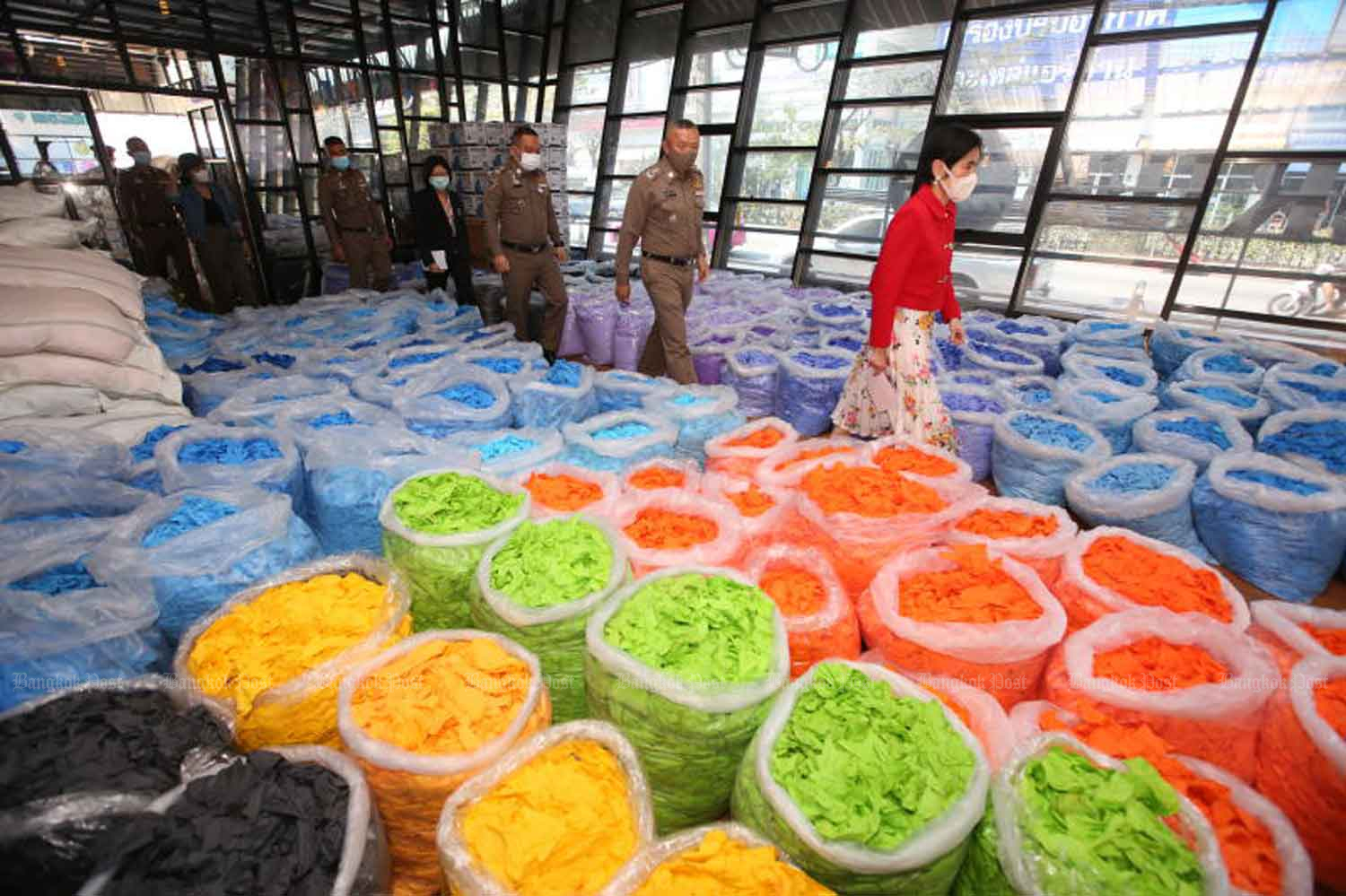 Food and Drug Administration and Royal Thai Police officers raid two warehouses in Nong Khaem district, Bangkok, on Wednesday after hearing they were being used to store used rubber gloves amid the coronavirus pandemic. Officers found 200 million baht worth of used gloves - some of which had already been washed and were ready to be resold - in the raid. An investigation is underway to find out who imported the gloves. (Photo: Pattarapong Chatpattarasill)