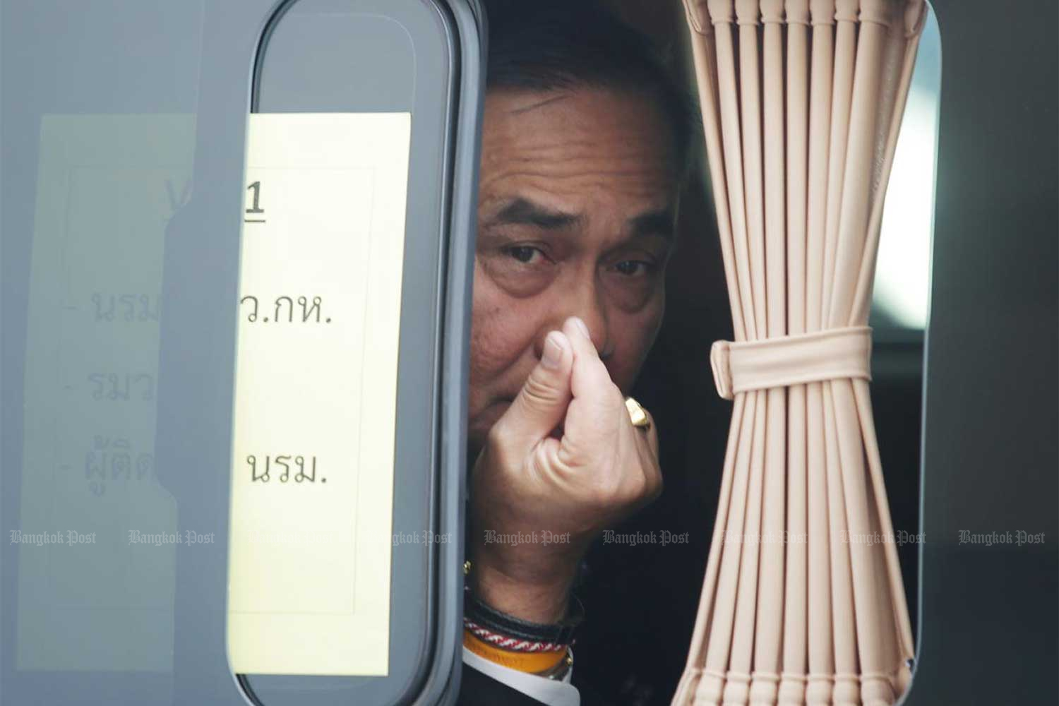 Prime Minister Prayut Chan-o-cha gives a mini heart gesture as he leaves the Armed Forces Academies Preparatory School in Nakhon Nayok in January last year. Political observers say the Prayut administration will face a tough year this year as it has to face the impact of the Covid-19 and charter amendments. (Photo by Apichit Jinakul)