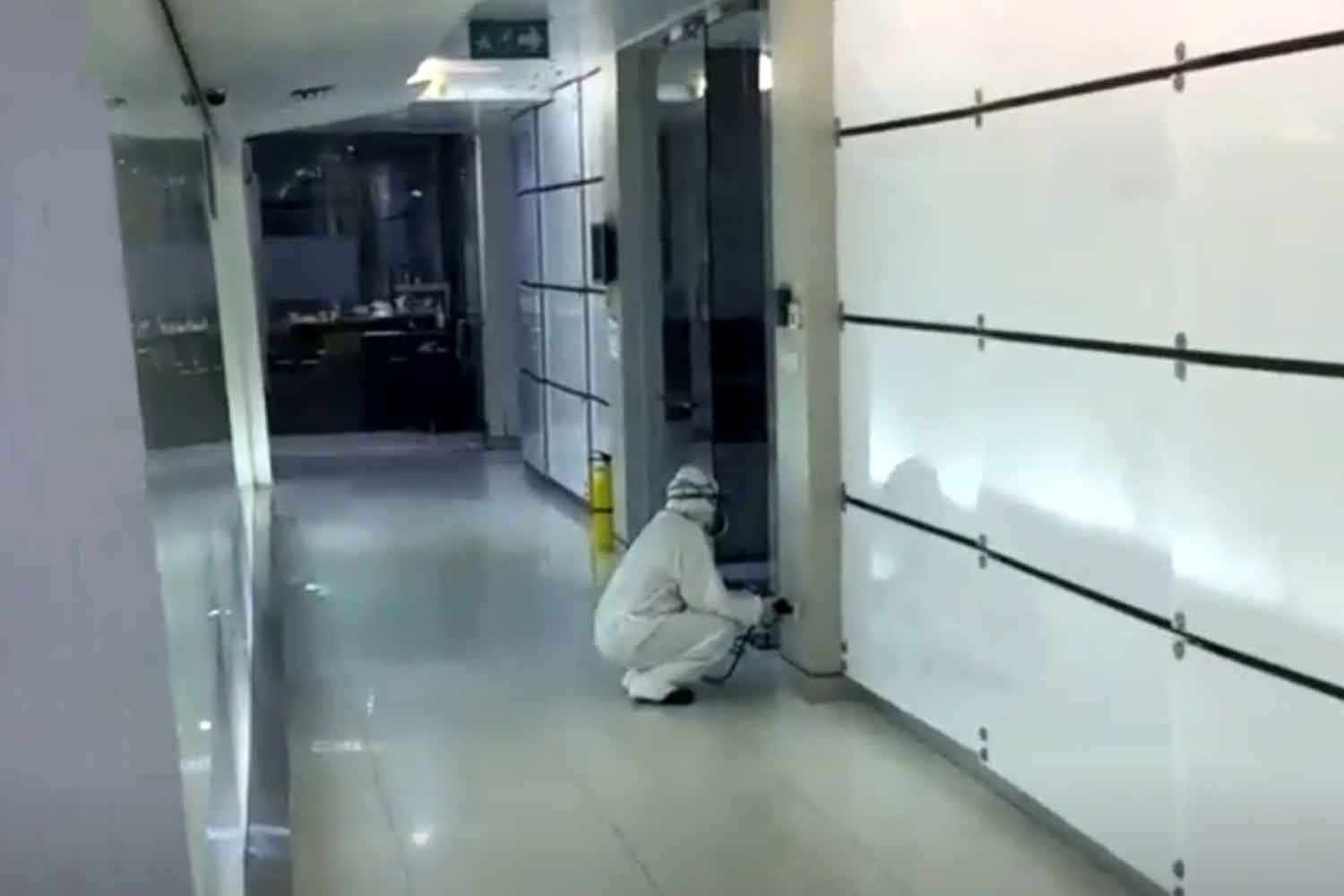 A disease control worker disinfects the Maleenon 2 Building of TV Channel 3 on Rama IV Road in Bangkok on Thursday night. (Screenshot from TV Channel 3)