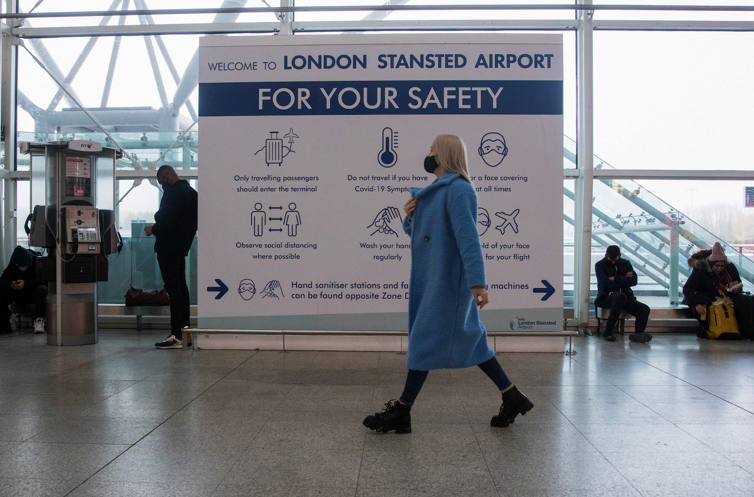 A passenger walks past a public health information board at London Stansted Airport on Friday. (Bloomberg Photo)