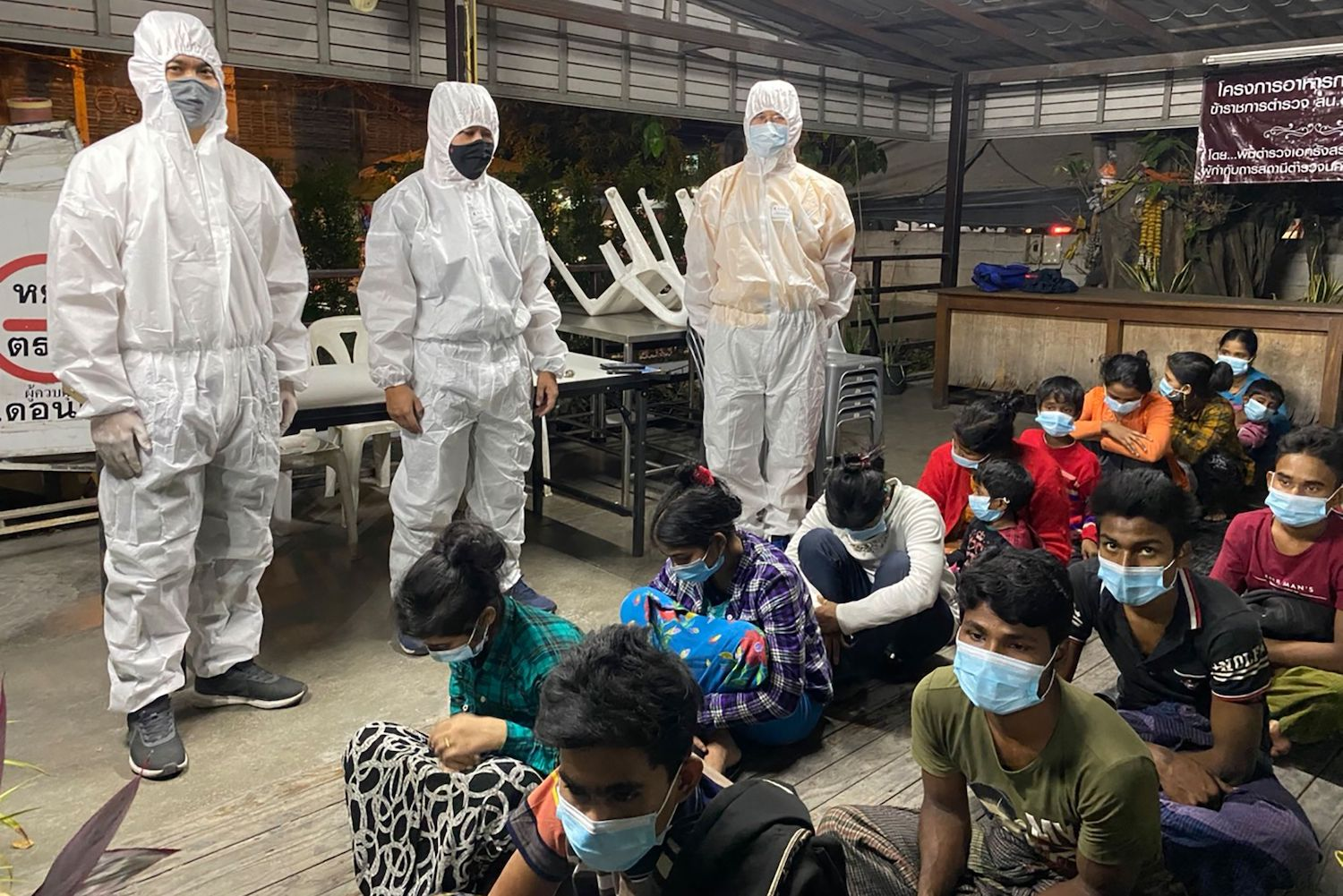 A picture taken by the Immigration Bureau on Jan 3 and released on Saturday shows immigration officers watching over a group of Rohingya migrants who were arrested in Don Muang district of Bangkok after being smuggled overland from Rakhine state in Myanmar. (Immigration Bureau handout via AFP)