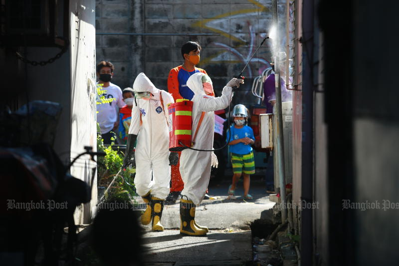 Officials spray disinfectant in a community in Klong Toey area on Saturday. (Photo by Somchai Poomlard)
