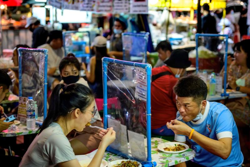 People dine separated by dividing screens at a street food corner in Bangkok's Chinatown on Sunday after authorities imposed restrictions on restaurants due to the recent Covid-19 coronavirus outbreak. (AFP photo)