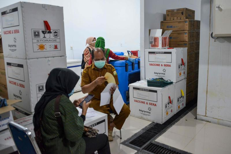 Indonesian health staff check Sinovac vaccines for the Covid-19 coronavirus at a storage facility before they are distributed to other provinces, in Banda Aceh on Jan 5, 2021. (AFP file photo)
