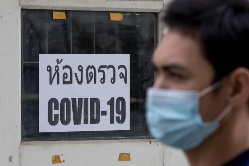 A man wearing a face mask walks past a Covid-19 examination room sign after taking a PCR test at the Urban Institute for Disease Prevention and Control in Bangkok on Monday. (Photo: AFP)