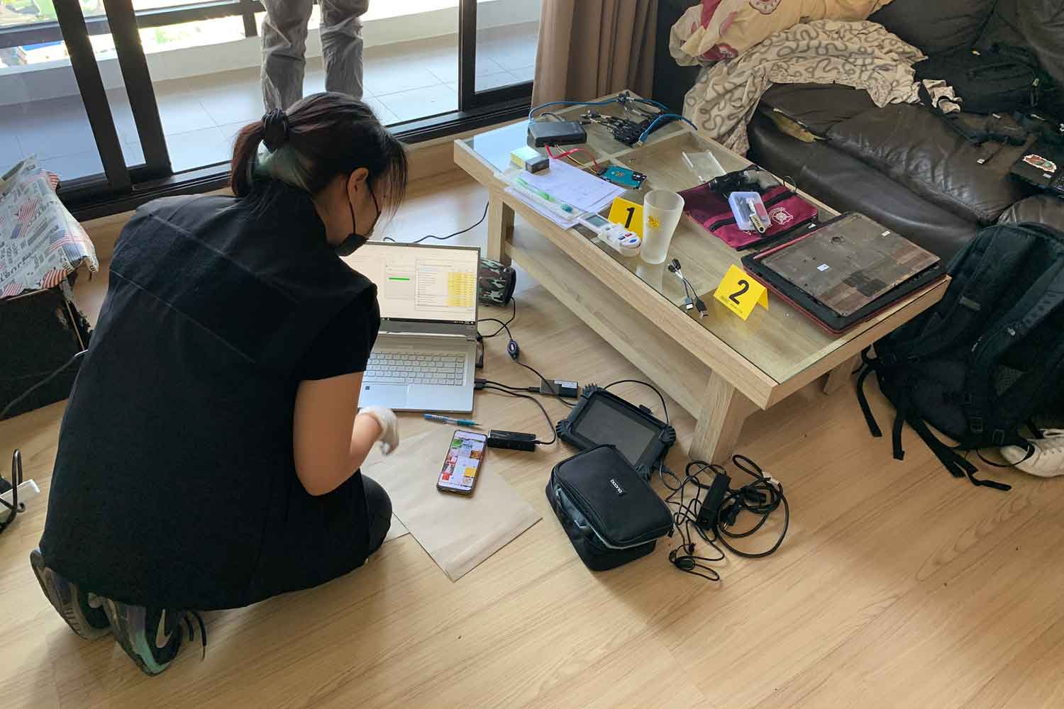 A Department of Special Investigation official examines the contents of a laptop found in a room of an apartment in Khlong San area, Bangkok. The Israeli tenant was arrested and charged with possession of child pornography and child sex ause. (Photo supplied)