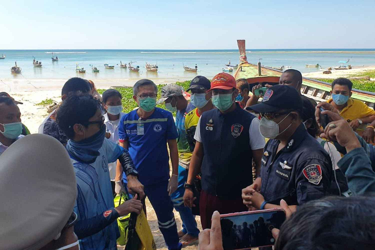 One of four people rescued after their boat capsized in the sea off Phuket, left, talks to marine police after being brought to Nai Yang beach in Thalang district. (Photo: Achadtaya Chuenniran)