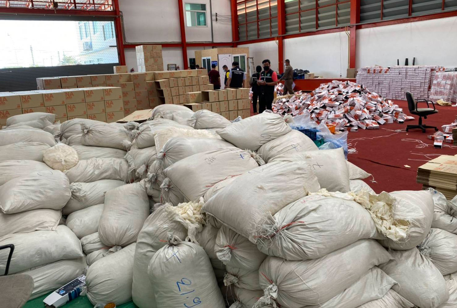 Consumer Protection police raid a illegal factory in Pathum Thani's Lam Luk Ka district and seize used gloves being boxed for sale as medical-grade gloves. (Supplied photo via Wassayos Ngamkham)