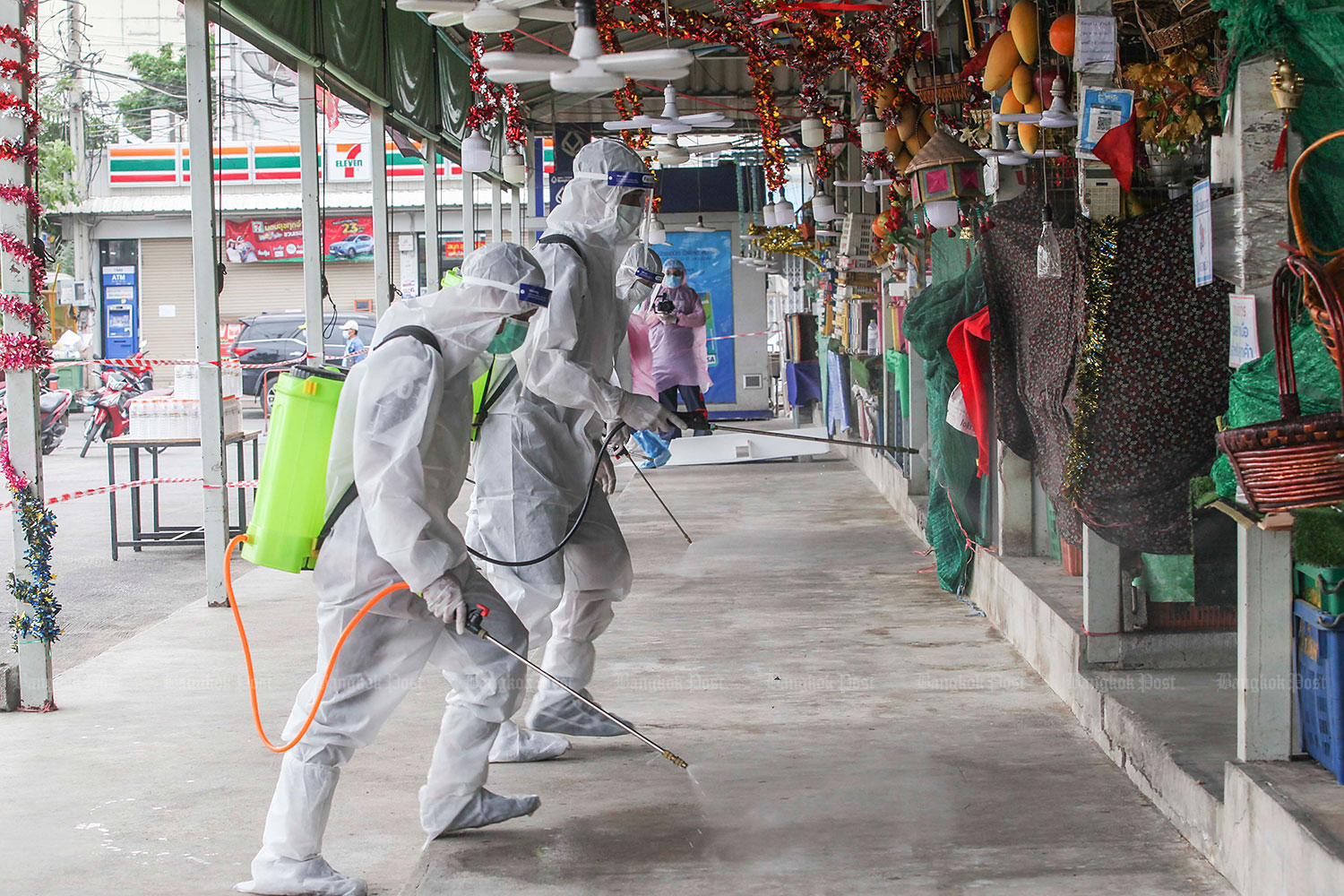 Officials in all full protective gear spray disinfectant on the pavement at Bang Yai central market which has reopened for business after 14 days. The market in Nonthaburi was designated as a maximum control zone after being linked with Covid-infections late last year. (Photo by Pattarapong Chatpattarasill)