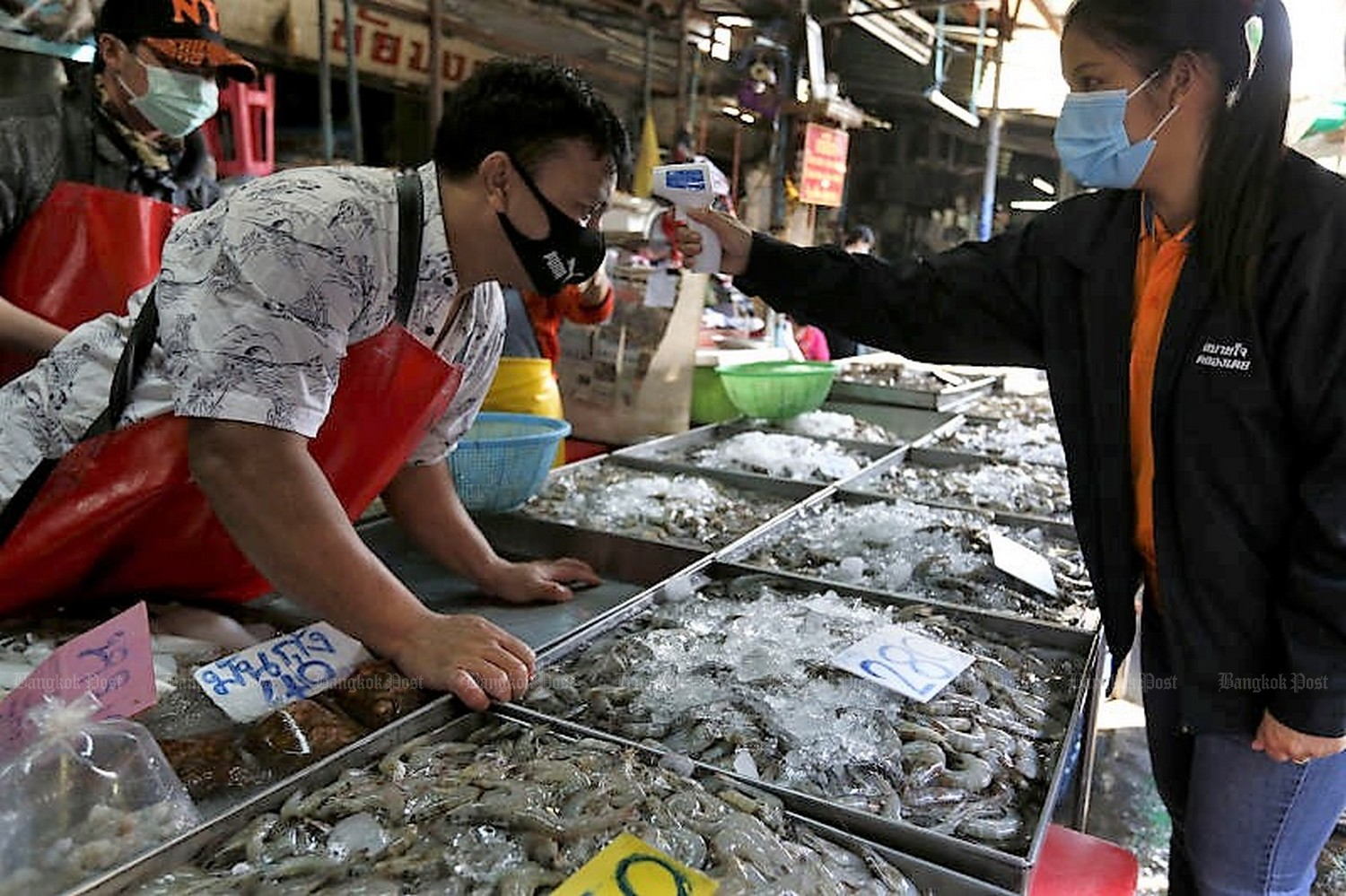 An official from Klong Toey District Office checks the temperature of a seafood vendor at Klong Toey market.