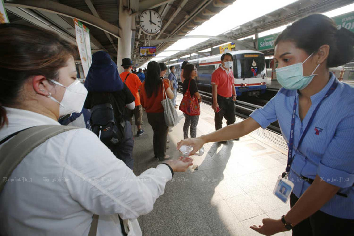 Skytrain commuters have their hands sanitised at Mor Chit BTS station as part of the prevention measures against the spread of Covid-19. (Bangkok Post file photo)