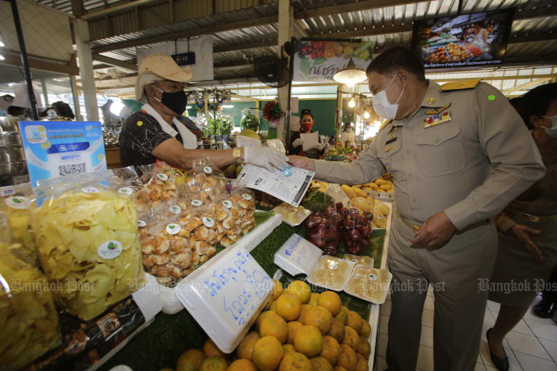 Bangkok governor Aswin Kwanmuang talks to a vendor during his visit to Or Tor Kor Market in Bangkok's Chatuchak district on Dec 21, 2020 during a campaign to limit transmission of Covid-19. (Photo by Pornprom Satrabhaya)