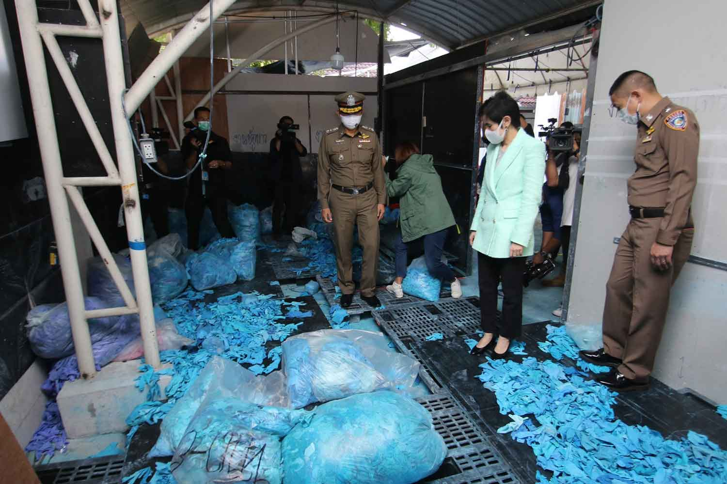 Officials inspect piles of fake medical gloves during a raid at a rented luxury house in Wang Thonglang district, Bangkok, on Wednesday. (Photo supplied)
