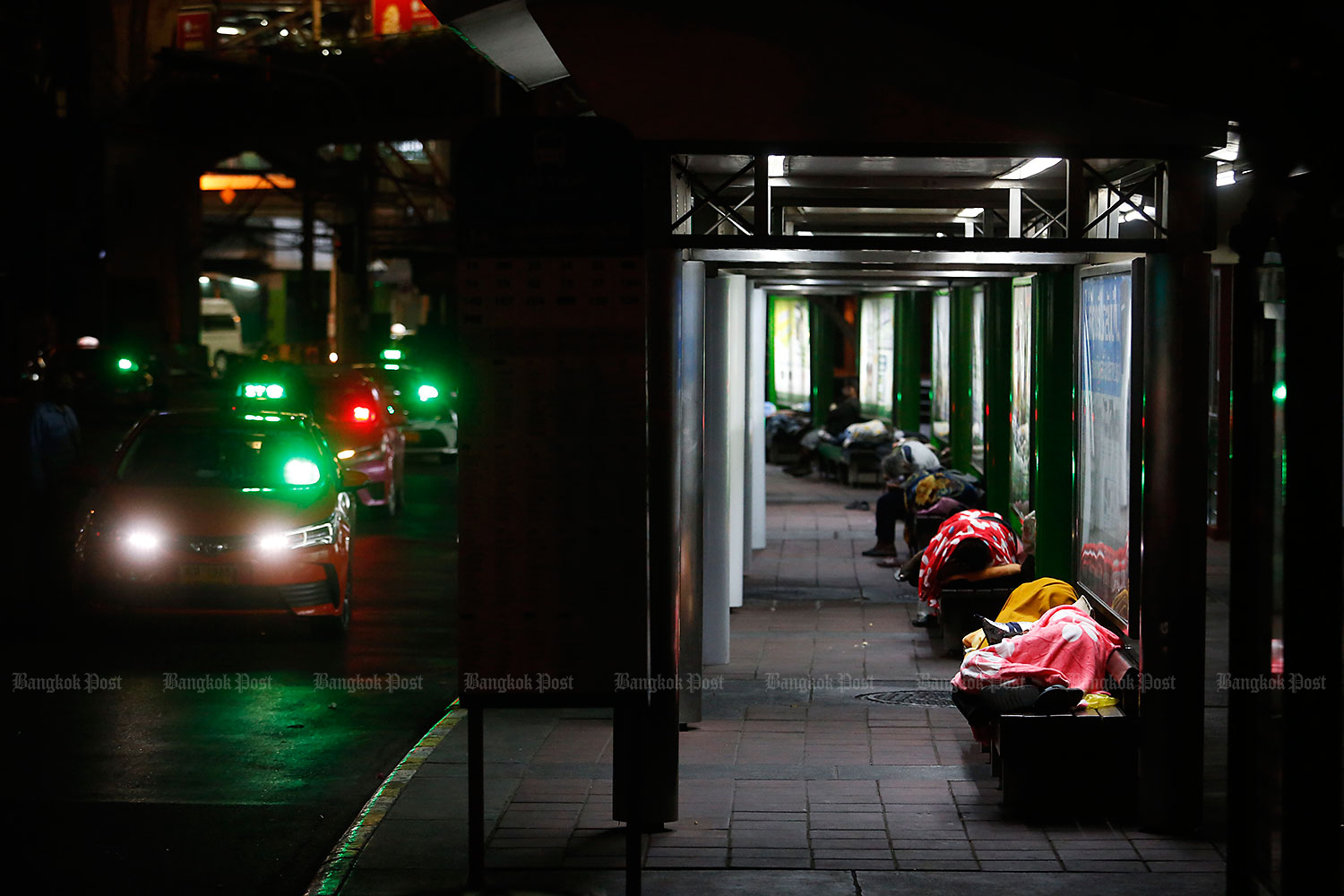 Feeling the chill: Homeless people bundle up with blankets at a bus stop near the Victory Monument on Tuesday night, when temperatures in the capital dipped to 16 degrees Celsius. The cool spell is expected to last for a few more days. (Photo by Wichan Charoenkiatpakul)