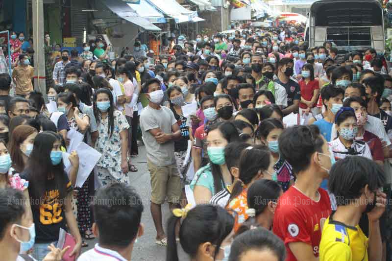 Around 2,000 Myanmar migrant workers wait in front of a dormitory in Samut Sakhon last month. Health officials were testing Thai vendors and Myanmar workers linked to a cluster of infections at the Central Shrimp Market. (Photo by Arnun Chonmahatrakool)