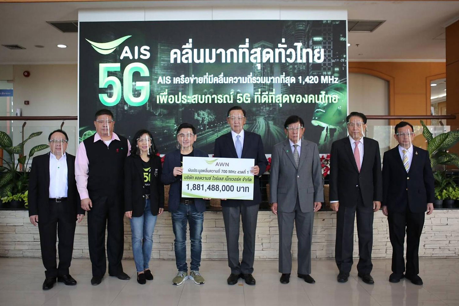 Mr Somchai (centre left) presents the payment of the first instalment of 1.88 billion baht for the 700MHz band to the NBTC.