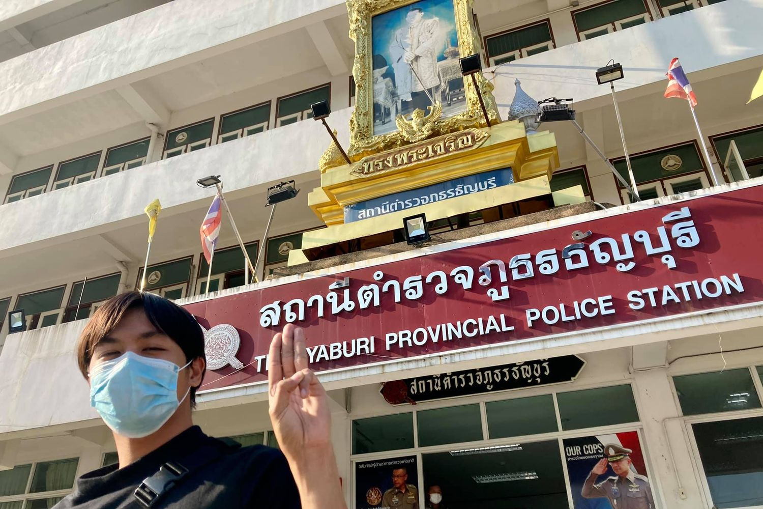 """Sirichai """"New"""" Natueng, a Thammasat University student, shows a three-fingered salute in front of the Thanyaburi police station on Thusrday. (Photo from United Front of Thammasat and Demonstration Facebook)"""
