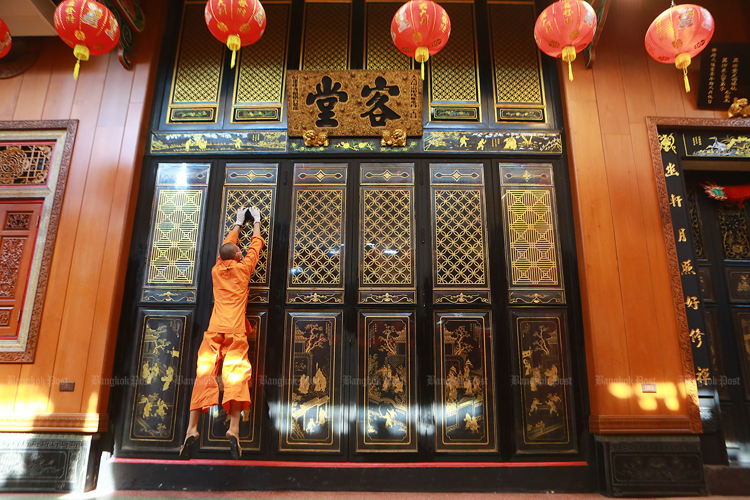 Clean and stretch: A novice jumps to clean door panels at Wat Mangkon Kamalawat in Bangkok's Yaowarat area. The Chinese temple is closed every Friday for a deep cleaning and disinfection of the premises to help curb the spread of Covid-19. (Photo by Somchai Poomlard)