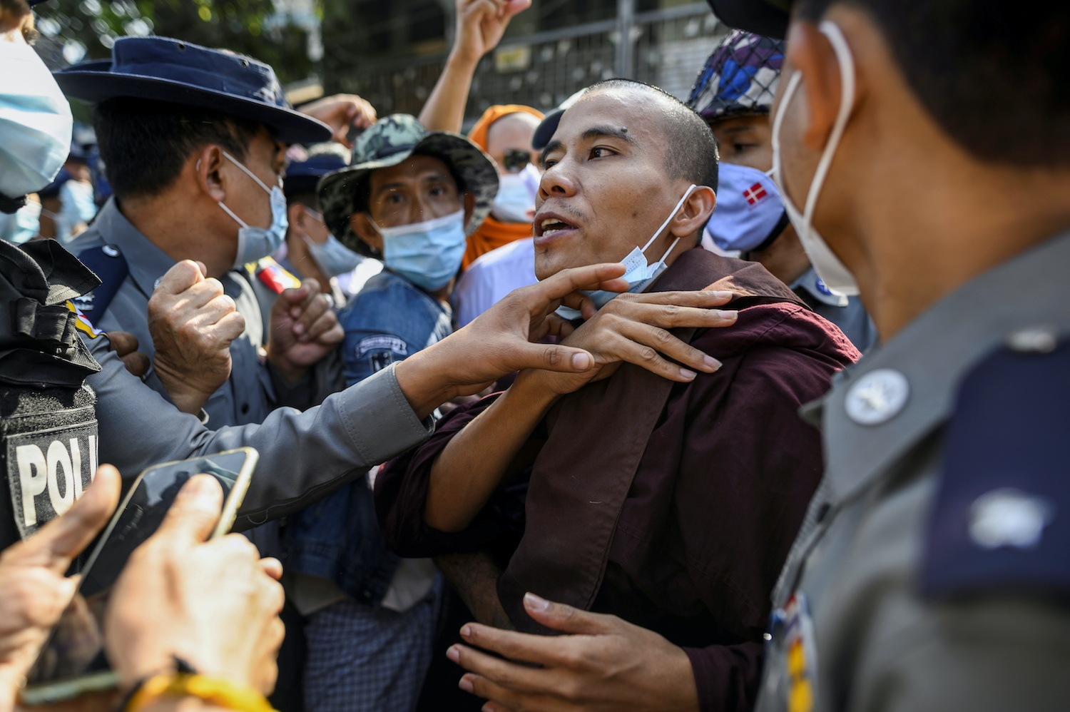 Police confront a monk taking part in a protest in support of the jailed nationalist monk Wirathu outside Insein prison in Yangon on Saturday. (Reuters Photo)