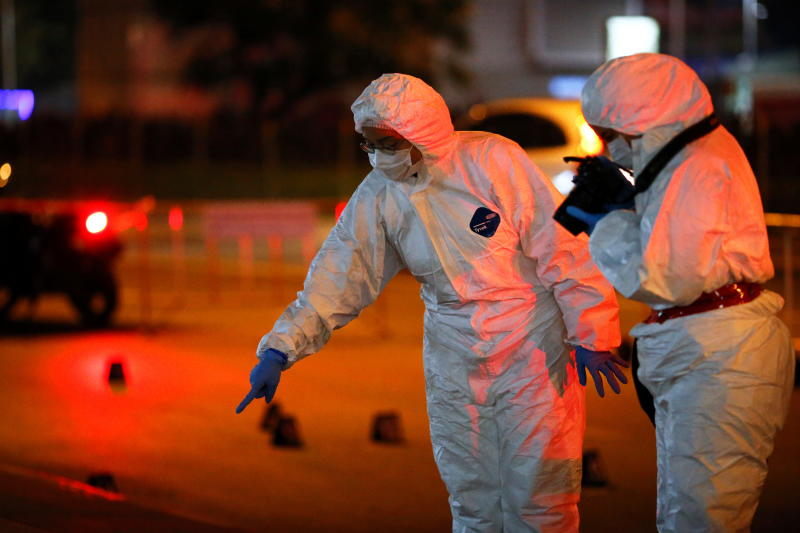 Police officers wearing PPE investigate at a blast site outside Chamchuri Square on Rama IV Road on Saturday. (Reuters photo)