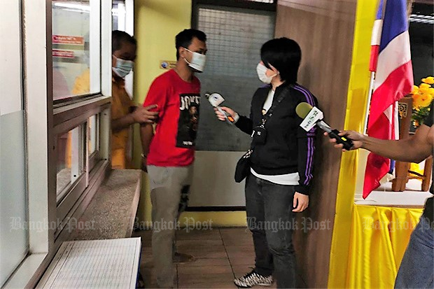 Reporters try to question k-powdered milk suspect Amornthep Chalermwat, alias Un Kiwi, (red shirt) after police take him into custody.