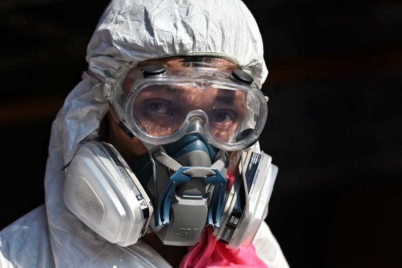 A man wearing personal protective equipment (PPE) prepares to spray disinfectant around Klong Toey fresh market after it was temporarily shut down due to several vendors testing positive for the Covid-19 novel coronavirus, in Bangkok on Jan 14, 2021. (AFP file photo)