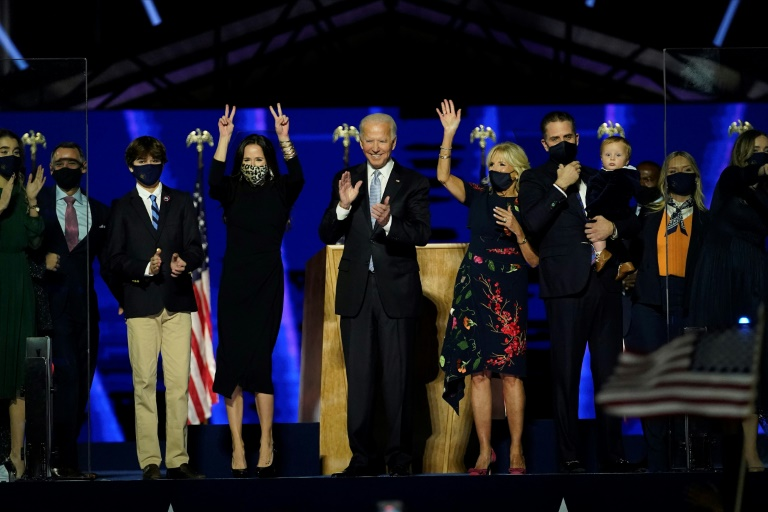 US President-elect Joe Biden (C) with his wife Jill Biden and members of their family salute the crowd on stage after delivering remarks in Wilmington, Delaware, on November 7, 2020