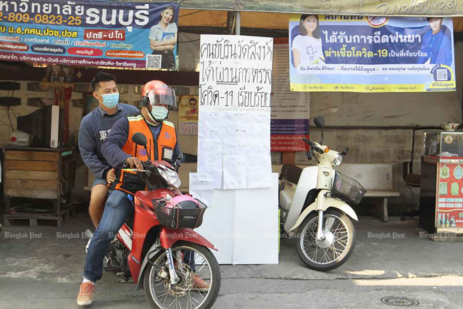 A taxi motorcyclist picks up a passenger on Soi Wat Sing in Chom Thong district of Bangkok on Tuesday, with a poster hung at the stand saying drivers there have been tested for Covid-19. (Photo: Arnun Chonmahatrakool)
