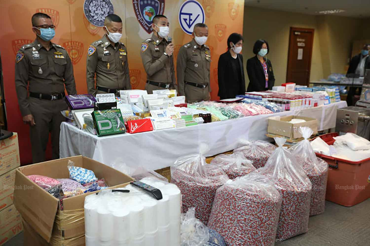 Consumer protection police and Food and Drug Administration officials show the large quantity of illegal medicines, beauty products, food supplements and ingredients seized during the raid in Nakhon Pathom on Tuesday. (Photo: Varuth Hirunyatheb)