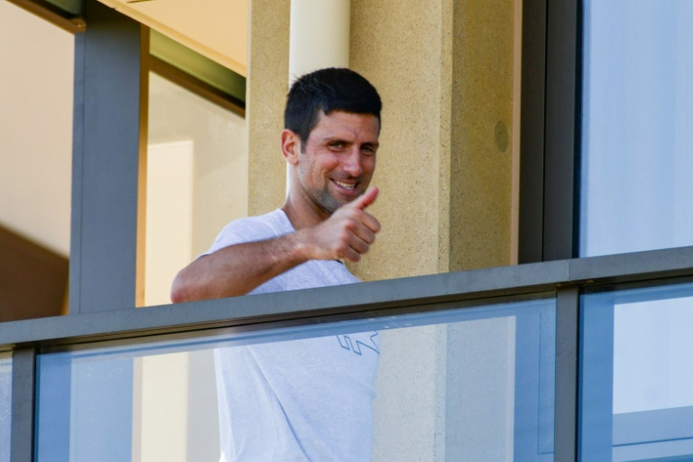 Under-fire: Novak Djokovic gestures from his hotel balcony in Adelaide, one of the locations where players are quarantined for two weeks ahead of the Australian Open in Melbourne