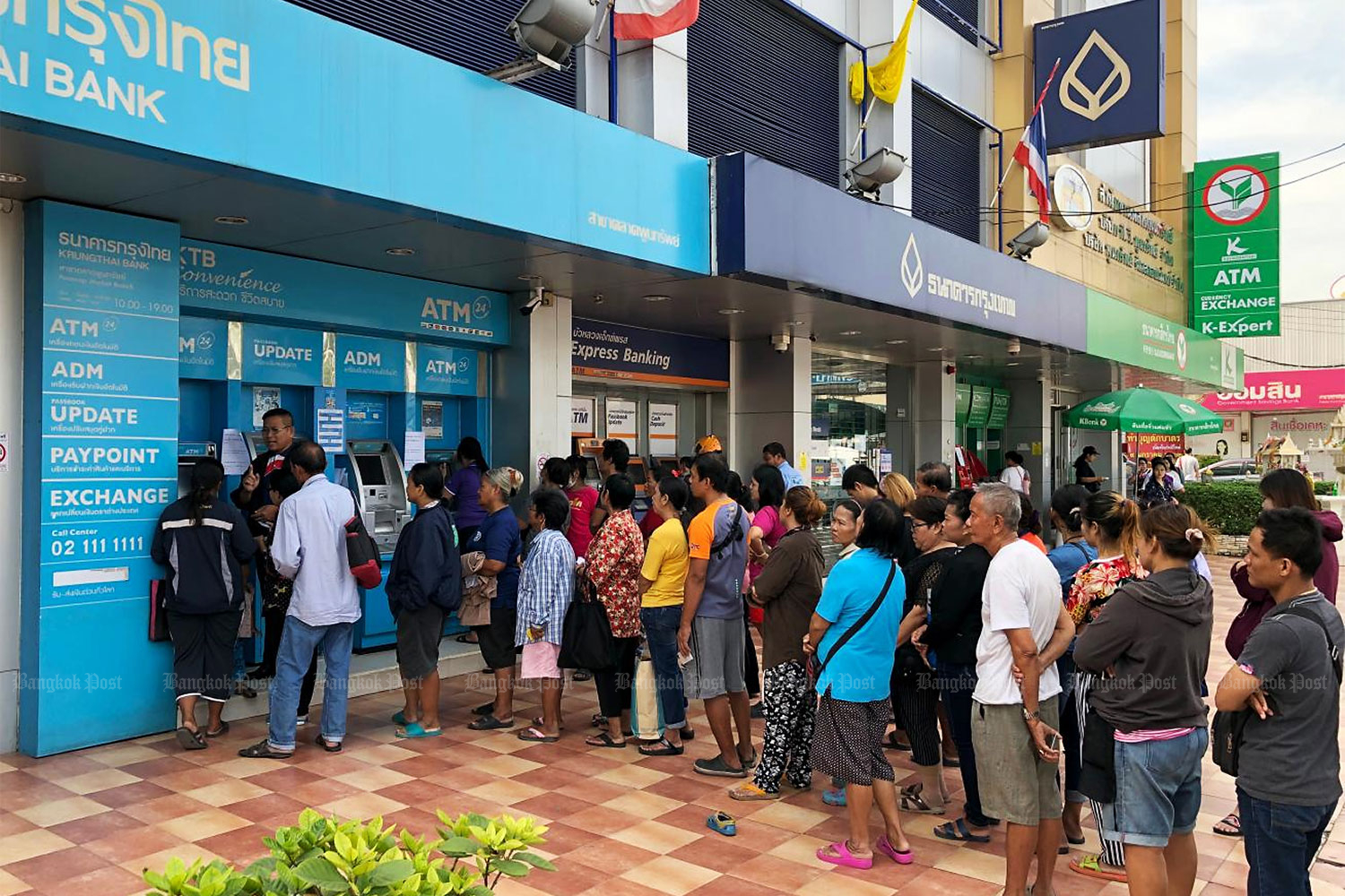 Welfare cardholders queue up to get cash at a Krungthai Bank ATM in Pathum Thani in December last year. (Photo by Sarot Meksophawannakul)