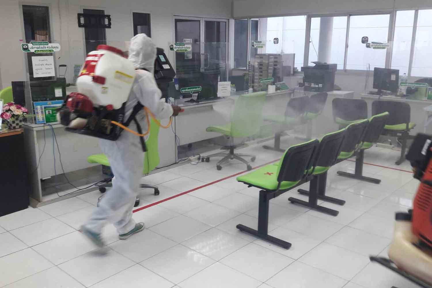 A disease control worker sprays disinfectant at a branch of the Bank for Agriculture and Agricultural Cooperatives in That Phanom district of Nakhon Phanom on Thursday. (Photo: Pattanapong Sripiachai)