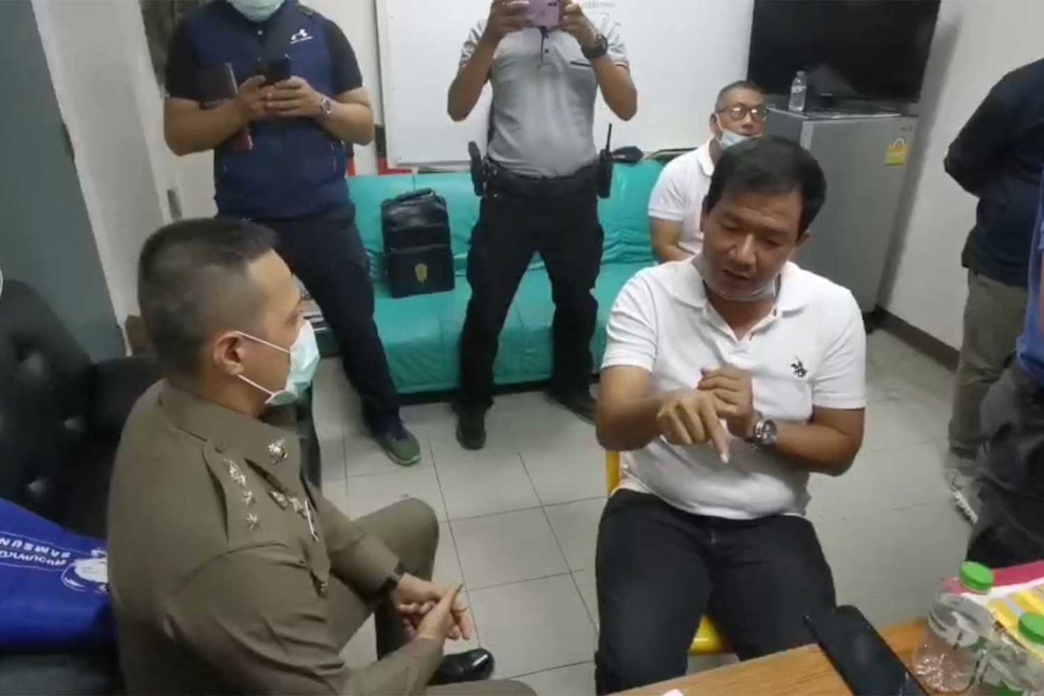 Thawatchai Ruengrit, 41, white T-shirt, turns himself to Pol Col Akkhawut Thaneerat, chief of Hat Yai police, in Songkhla on Thursday, following a shooting in which one man was killed and two others wounded on Wednesday night. (Photo: Assawin Pakkawan)