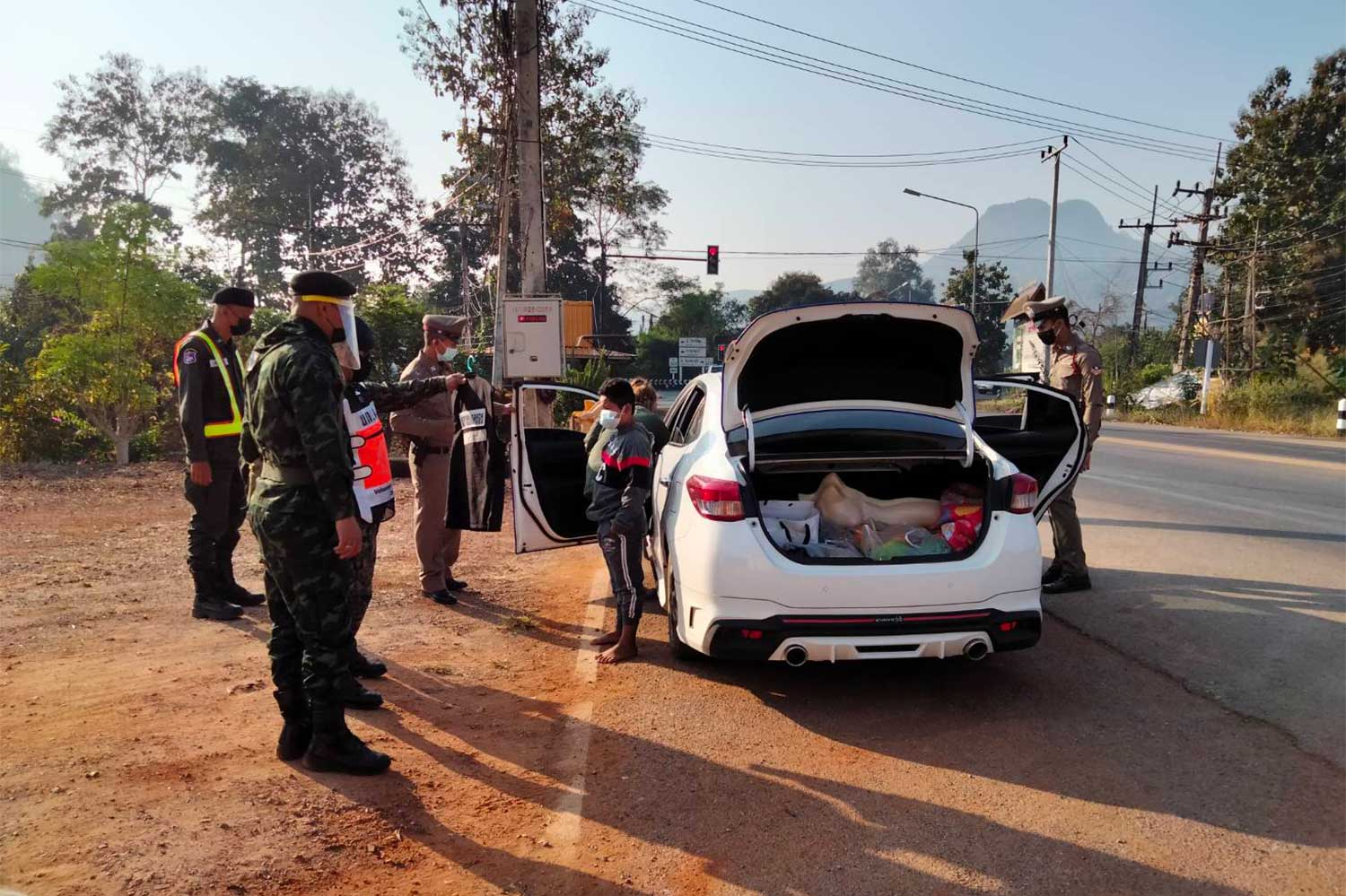 Officers search a Toyota Yaris driven by a woman and find four illegal Myanmar migrants,  at a road checkpoint in Thong Pha Phum district, Kanchanaburi, on Friday. (Photo:  Piyarat Chongcharoen)
