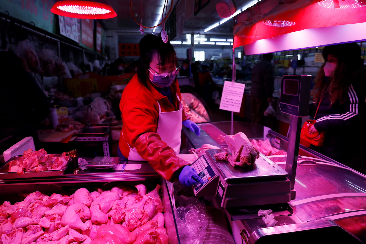 A food vendor weighs a chicken at her stall inside a market in Beijing on Jan 15. (Reuters Photo)