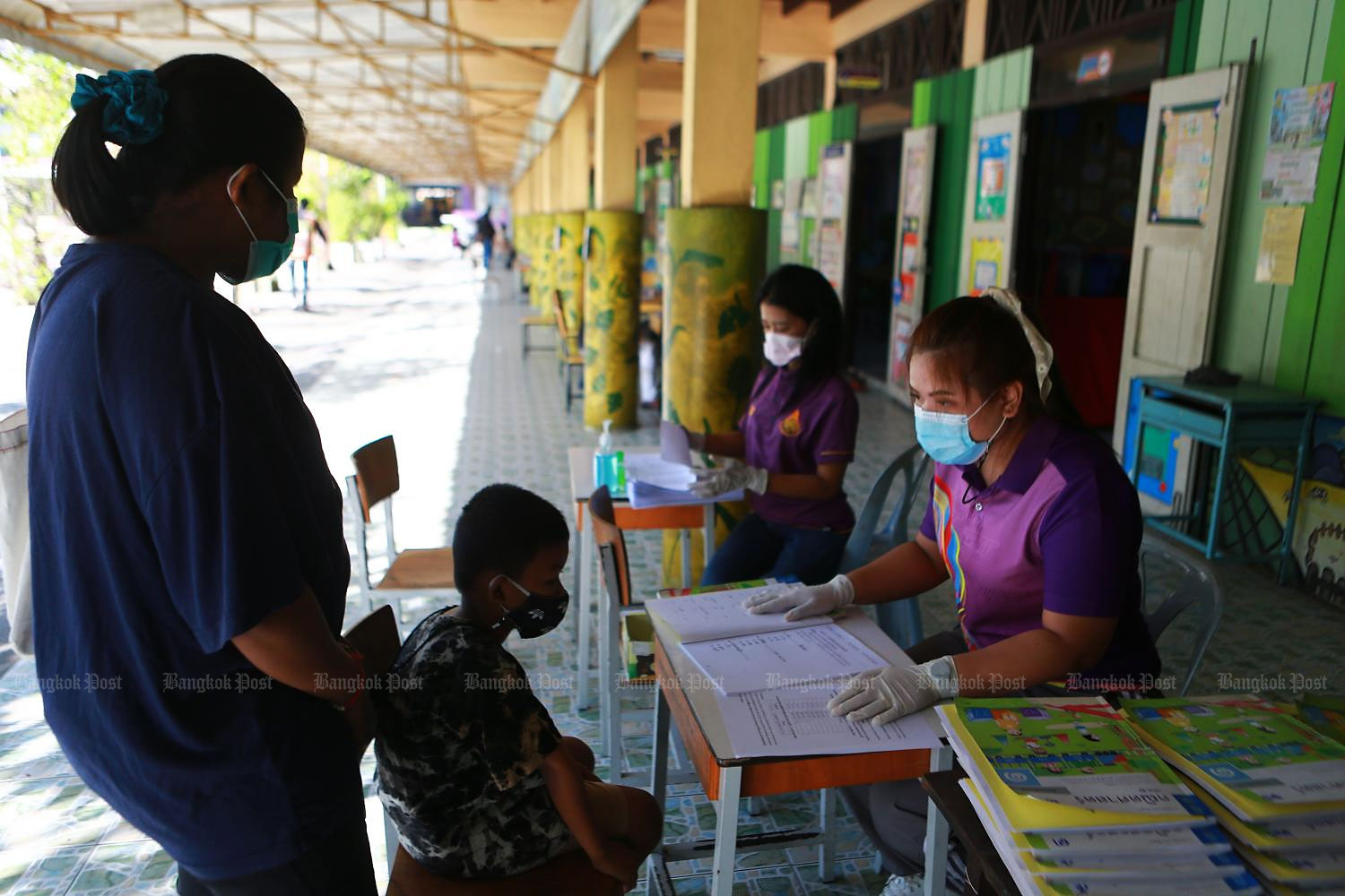 In this Jan 5 photo, a student and his mother drop by at his school in Samut Prakan to pick up educational material to study at home after the government ordered school closures in response to a new wave of Covid-19 infections.(Photo by Somchai Poomlard)