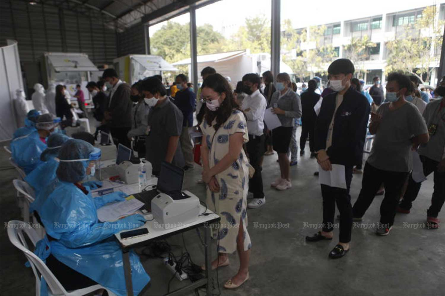 Health officials conduct Covid-19 testing among staff at the National Broadcasting Service of Thailand (NBT) TV channel on Friday after a news anchor was infected. (Photo by Nutthawat Wicheanbut)