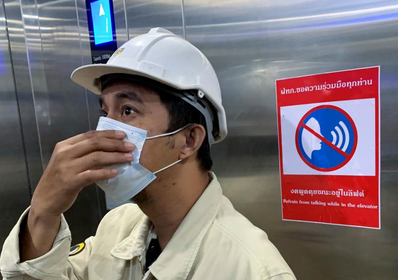 A worker adjusts his face mask as a preventive measure against the Covid-19 coronavirus inside an elevator with a restriction notice in Bangkok on Jan 18, 2021. (AFP file photo)