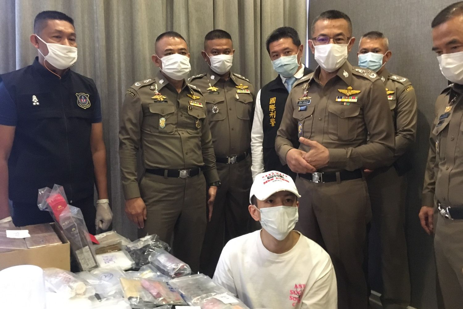 Police arrest Chou Yi Shen (seated) at a condominium in Ratchathewi district in Bangkok on Monday. (Royal Thai Police photo)