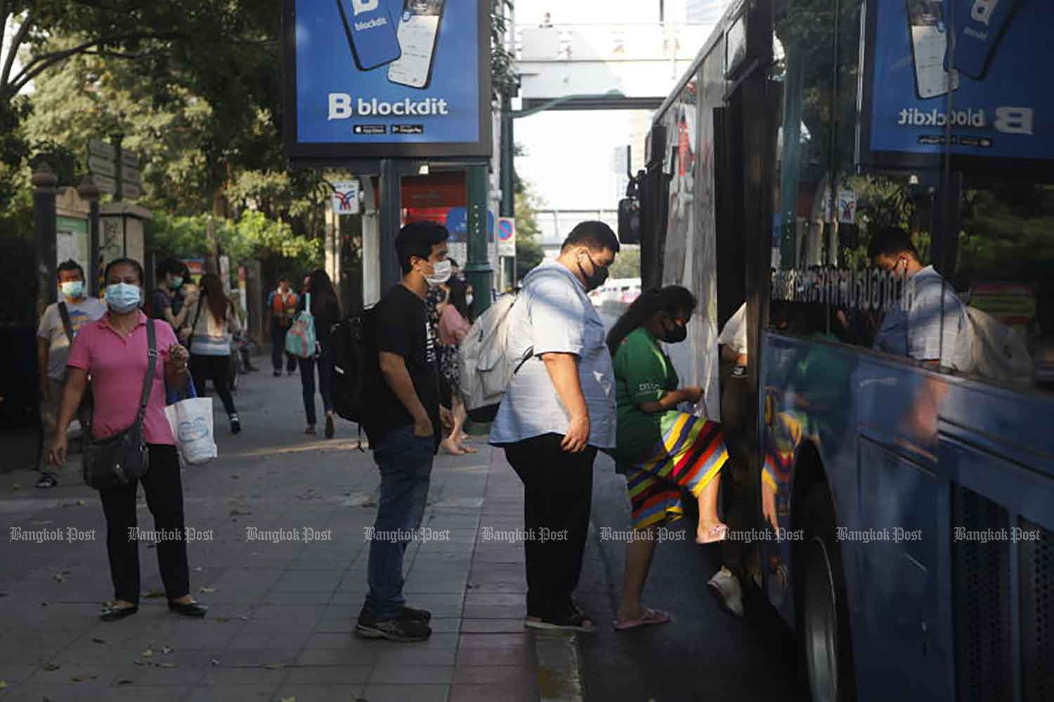 Commuters wearing face masks board a bus in Chatuchak district of Bangkok on Tuesday, when 819 new cases of Covid-19 disease were detected. (Photo: Nutthawat Wicheanbut)