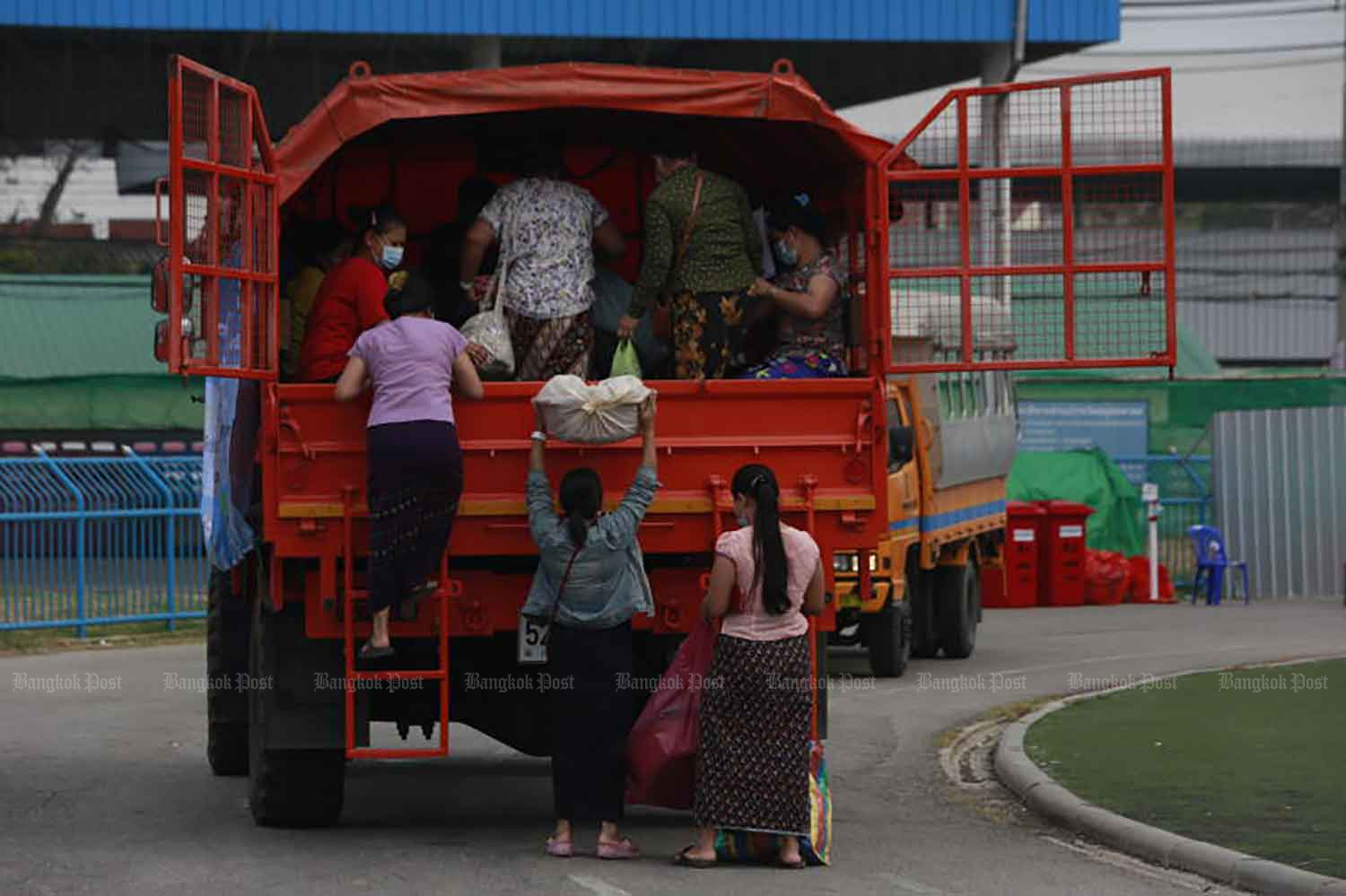 Migrant workers climb aboard their transpot as they are discharged from a field hospital in Samut Sakhon. The province will likely remain under the harshest business and activity restrictions next month, for Covid-19 control. (Photo: Arnun Chonmahatrakool)