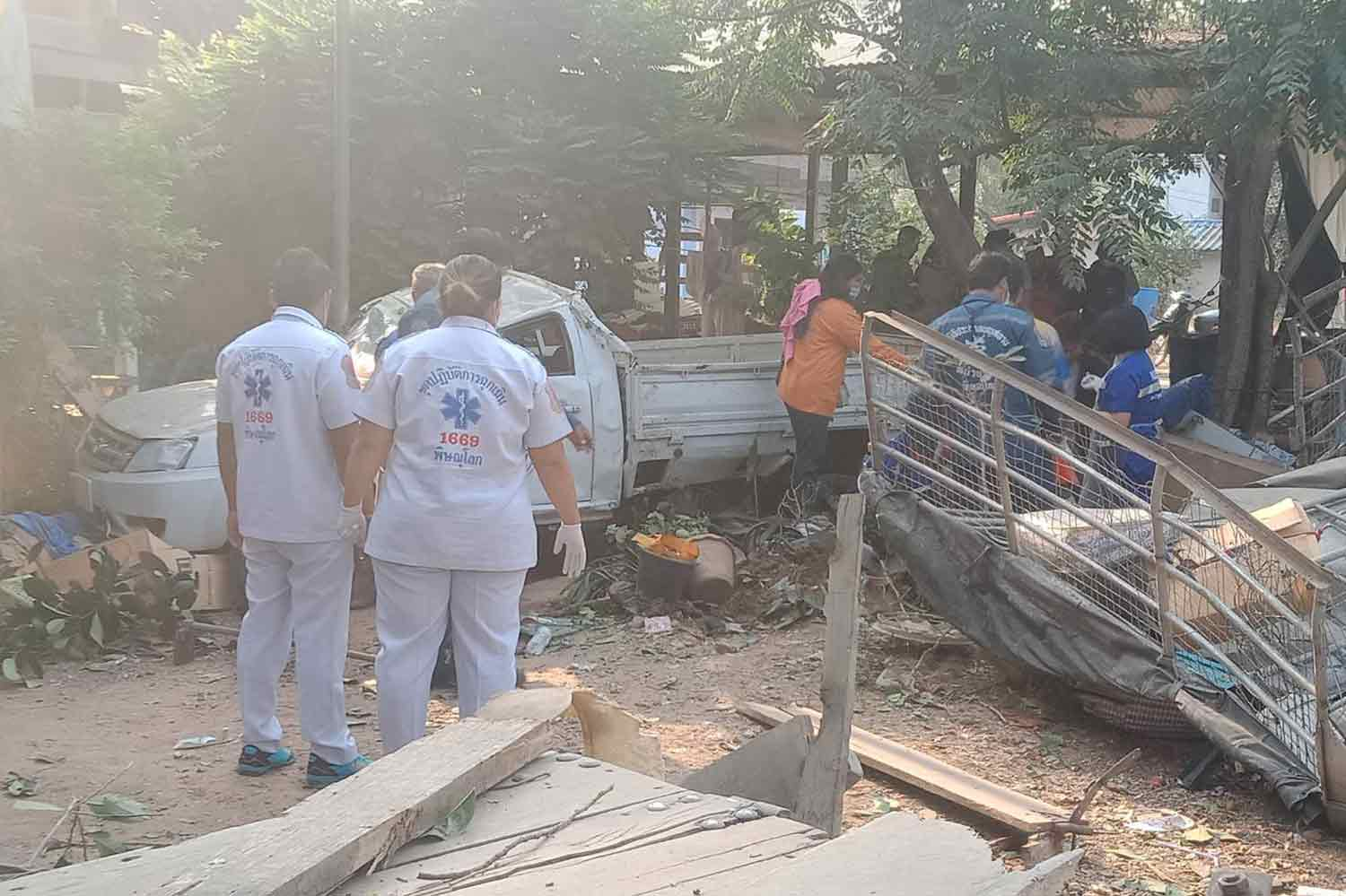 Rescuers with the pickup that ran off Highway 11 and crashed into a house in Phrom Phiram district, Phitsanulok. Five Myanmar workers were injured. (Photo: Chinnawat Singha)