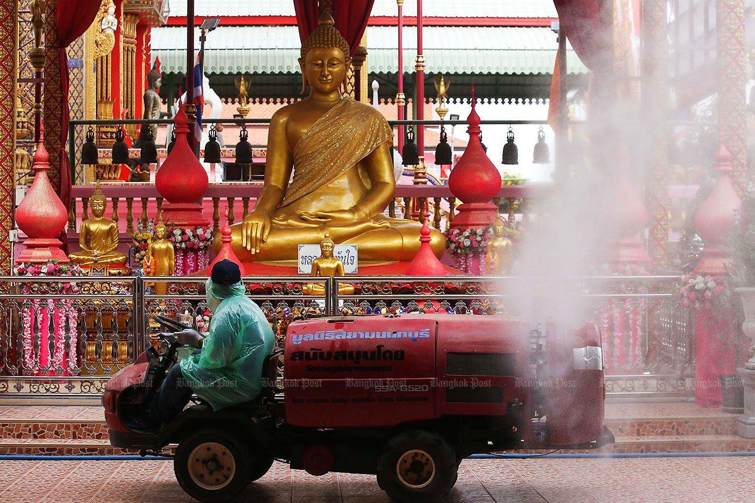 A worker operates a vehicle to spray disinfectant around Wat Ta Khien and the adjacent floating market in Bang Kruai district, Nonthaburi, on Wednesday. The cleaning was conducted ahead of Saturday's reopening of the temple and market, closed recently due to the new Covid-19 outbreak. (Photo by Pattarapong Chatpattarasill)