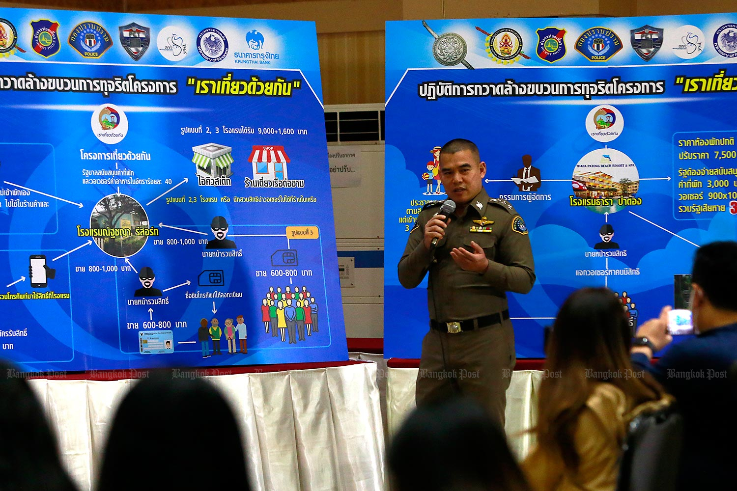 A police officer shows a chart detailing frauds involving the Rao Tiew Duay Kan (We Travel Together) co-payment scheme. (Photo by Arnun Chonmahatrakool)