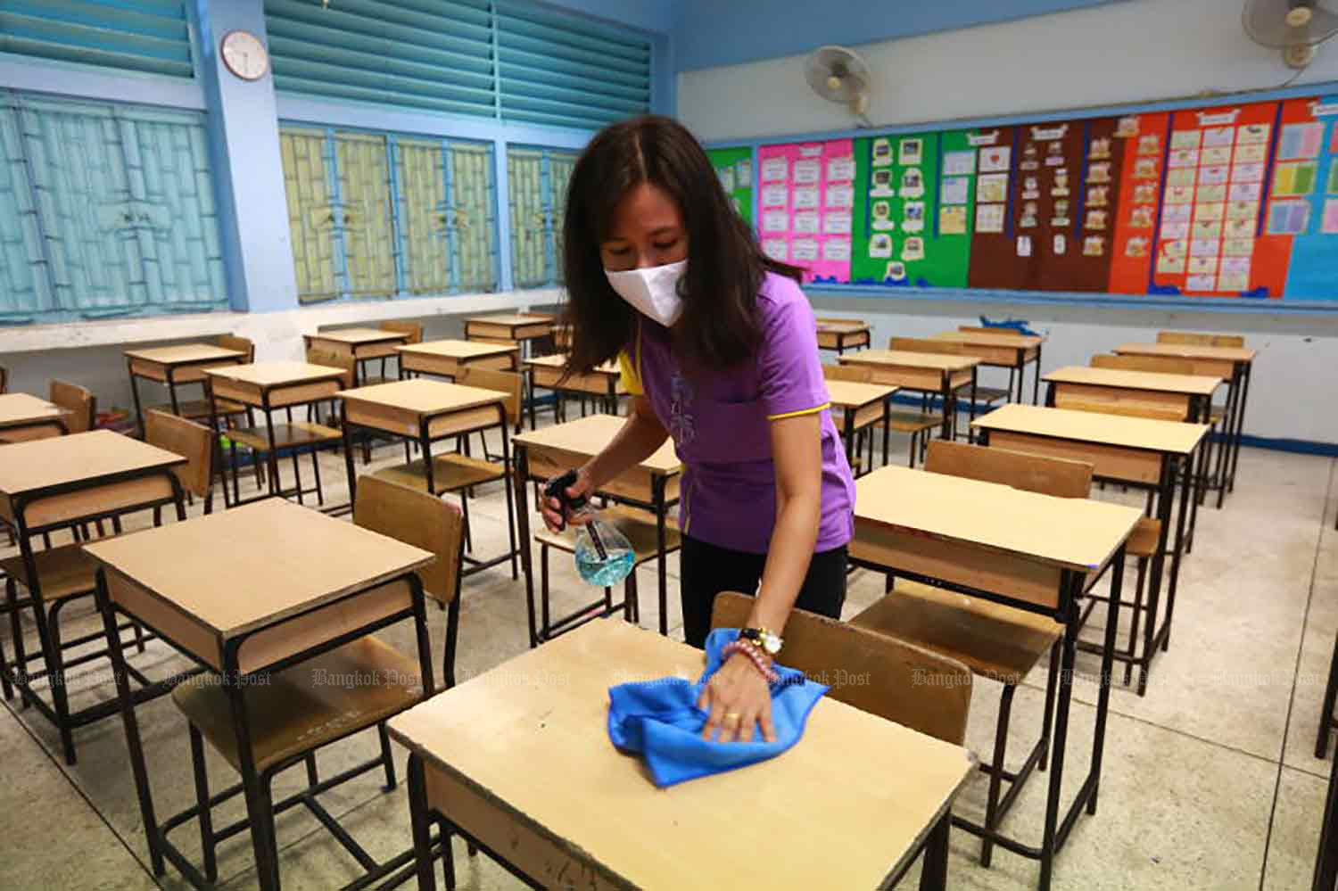 A worker cleans a classroom at Ban Bangkapi School in Bang Kapi district, Bangkok, on Thursday morning. The school is expected to reopen on Monday as the govenment eases Covid-19 restrictions. (Photo: Somchai Poomlard)